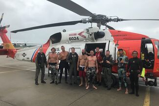 Coast Guard helicopter crew with rescued fishermen