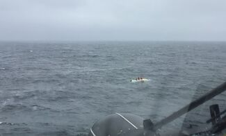 Coast Guard helicopter approaches overturned boat