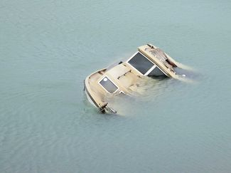 Capsized or Swamped: Stay with the Boat!